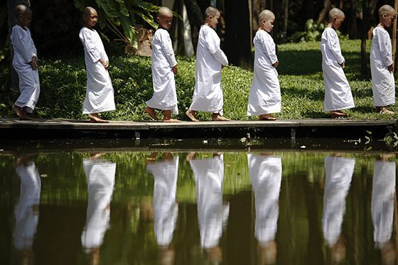 Novice nuns walk in the garden of the Sathira-Dhammasathan Buddhist meditation centre in Bangkok